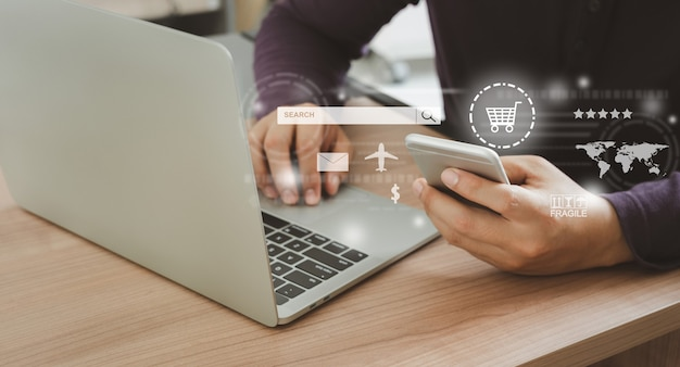 Mensch, der handy mit laptop verwendet. ideen über kundenbestellungen kaufen von händlerseiten über die internet-website. online-shopping, e-commerce und lieferservice, marketingsystem im globalen netzwerk .