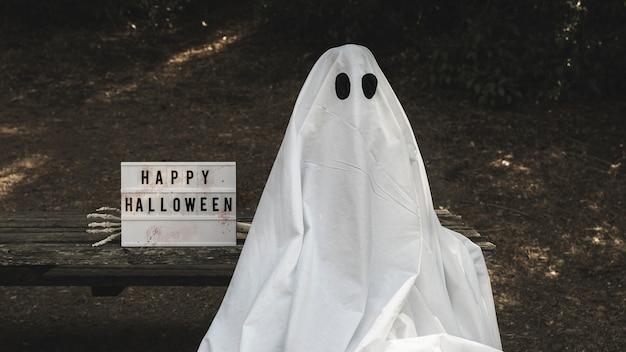 Mensch im geistanzug, der auf bank nahe halloween-tablette sitzt