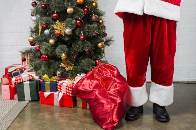Mensch in sankt anzug in der nähe von weihnachtsbaum