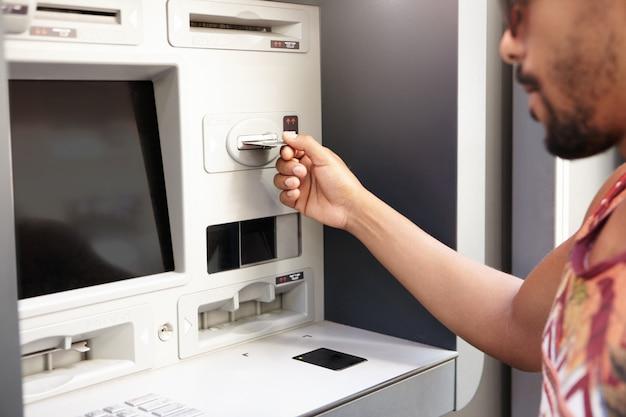 Mensch und technik. dunkelhäutiger mann mit geldautomat. die hand des schwarzen kerls, die plastikbankkarte in geldautomaten oder geldautomaten einführt