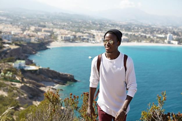 Menschen, aktiver lebensstil, reisen, abenteuer und tourismuskonzept. hübscher trendiger aussehender afroamerikanischer tourist mit rucksack, der urlaub im ausland verbringt