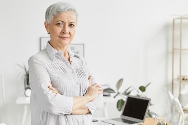 Menschen, alter, technologie und berufsbild. gut aussehende ernsthafte weibliche führungskraft mittleren alters mit kurzer pixie-frisur, die im büro mit verschränkten armen auf der brust steht, wobei ihre haltung vertrauen ausdrückt
