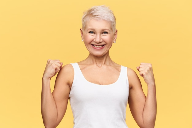 Menschen, alter, wohlbefinden und gesundheitskonzept. attraktive stilvolle reife frau, die weißes trägershirt trägt, das ihre muskulösen arme zeigt, fäuste ballt und breit lächelt, glücklichen energetischen blick habend