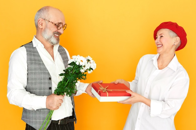 Menschen, altern, dating und romantik konzept. seitenansicht des hübschen eleganten älteren mannes in den gläsern, die bündel feldblumen und schachtel schokolade halten und geschenk zu seinem attraktiven reifen weiblichen datum geben