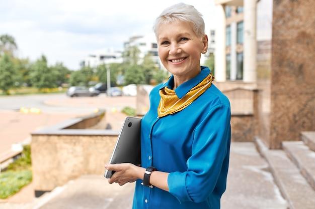 Menschen, altern, urbaner lebensstil, karriere- und technologiekonzept. stilvolle elegante geschäftsfrau mittleren alters, die laptop aufwirft, der außerhalb des bürogebäudes aufwirft, zum geschäftstreffen geht und in die kamera lächelt