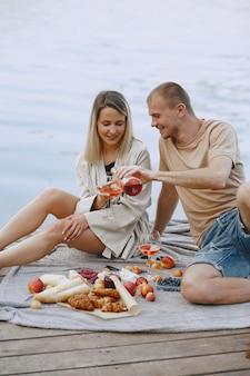Menschen am fluss. köstliches gesundes sommerpicknick auf dem rasen. früchte auf einer decke.