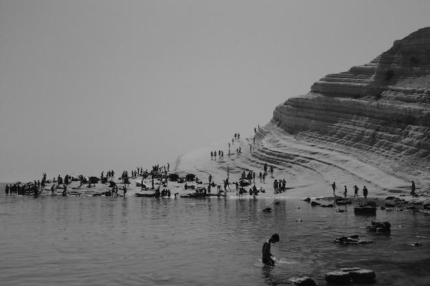 Menschen am strand in schwarz und weiß