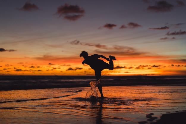 Menschen am ufer des ozeans bei sonnenuntergang. mann springt gegen den hintergrund der untergehenden sonne