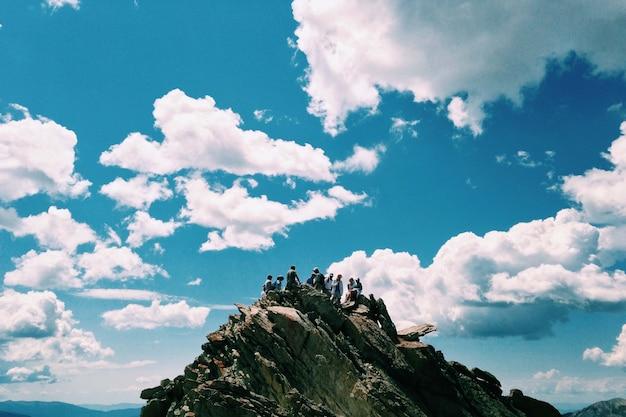 Menschen auf dem gipfel des berges über dem blauen himmel