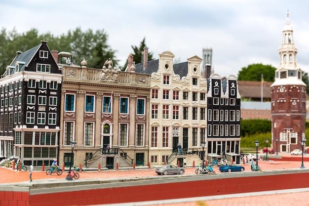Menschen auf der straße, altes gebäude, radfahrer, miniaturszene im freien, europa. mini-figuren mit hoher entkalkung von objekten, realistisches diorama
