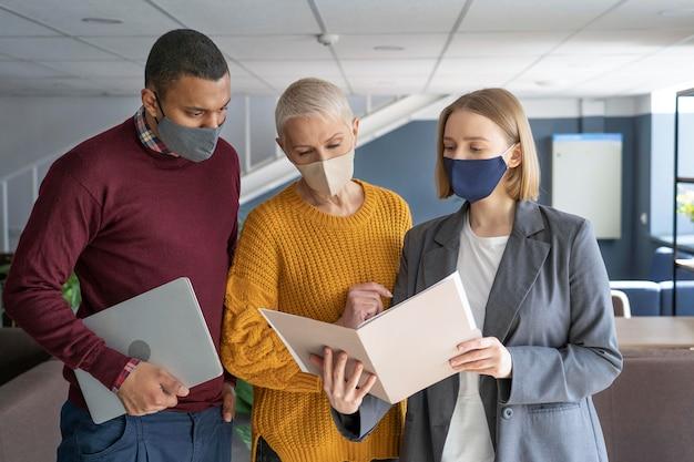 Menschen bei der arbeit, die medizinische masken tragen