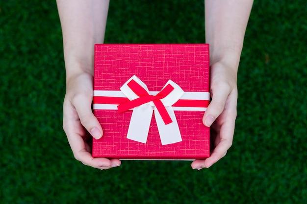 Menschen benutzen beide hände, um rote geschenkboxen, geschenkboxen für geburtstage, jubiläen, weihnachten zu halten. an wichtigen tagen und festen sind geschenke beliebt. eine wichtige geschenkidee für den tag.