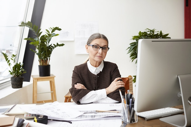 Menschen, beruf, beruf und alter. zuversichtlich professionelle ältere frau architektin in formellen kleidern und brillen, die an ihrem arbeitsplatz mit verschränkten armen sitzen, zeichnungen machen und cad-programm des pcs verwenden