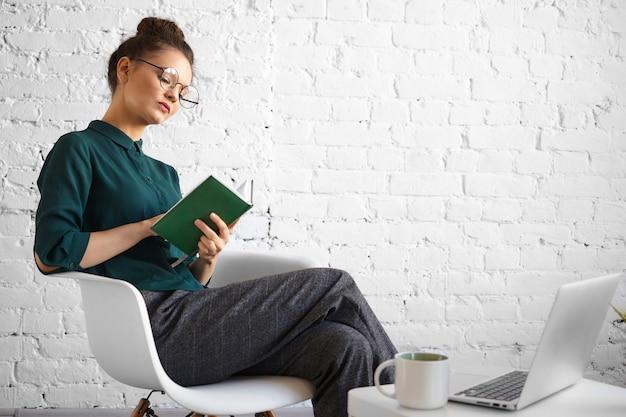 Menschen, beruf, technologie und modernes lifestyle-konzept. porträt der konzentrierten ernsten geschäftsfrau in der stilvollen brille, die entfernt im café arbeitet, im tagebuch schreibt, mit laptop und tasse sitzt