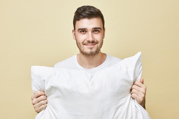 Menschen-, bett- und ruhekonzept. porträt des attraktiven glücklichen jungen mannes mit stoppeln, die lokal gehaltenes weißes kissen darstellen, das zum schlafen geht, mit positivem lächeln, das gute nacht sagt