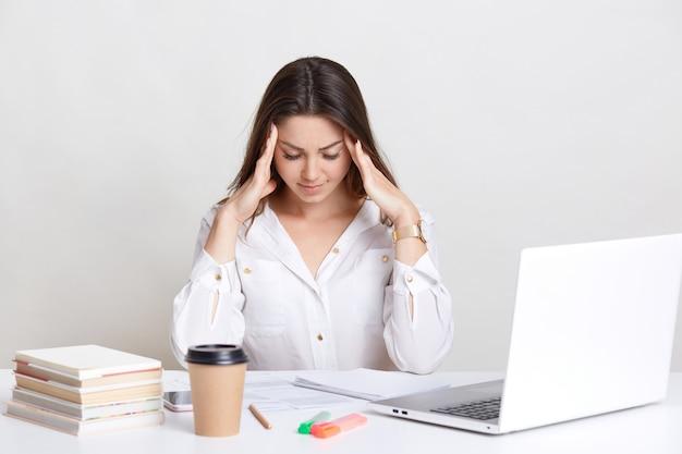 Menschen-, bildungs- und arbeitskonzept. müder arbeitgeber hält die hände auf dem kopf, konzentriert nach unten, trägt ein weißes hemd, sitzt am schreibtisch, benutzt einen laptop, trinkt heißen kaffee oder latte, isoliert an der weißen wand