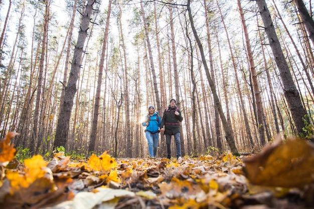 Menschen, campingausflug und naturkonzept - flachwinkelaufnahme des touristenpaares, das im wald wandert