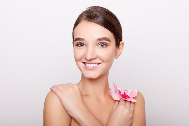 Menschen, dehydration, hautpflege und schönheitskonzept - schönes mädchen mit orchidee flowers.beauty model woman face. perfekte haut. professionelles make-up. schöne frau gesicht nahaufnahme porträt hände auf der haut