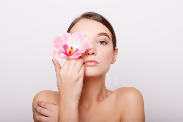 Menschen, dehydration, hautpflege und schönheitskonzept - schönes mädchen mit orchidee flowers.beauty model woman face. perfekte haut. professionelles make-up. schöne frauengesichtsnahaufnahmeporträthände auf der haut