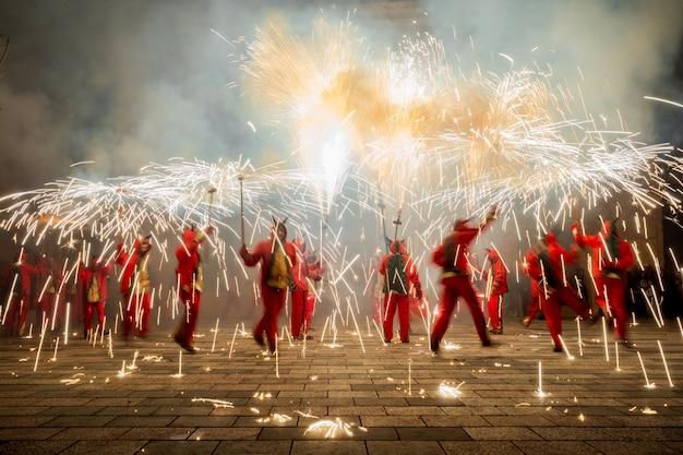 Menschen, die als dämonen verkleidet sind und mit feuerwerk tanzen