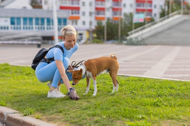 Menschen, die als hundesitter arbeiten, mädchen mit französischem pudelhund im park. die junge hispanische frau hebt den kot ihres haustieres mit plastiktüte auf.