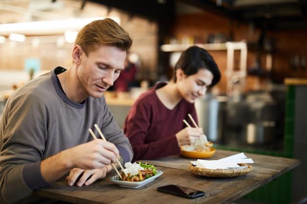 Menschen, die asiatisches essen im cafe genießen