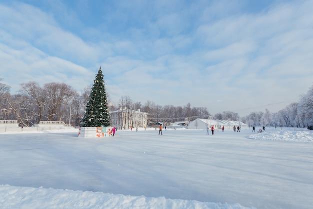 Menschen, die auf der eisbahn an einem sonnigen tag in sankt petersburg, russland skaten.