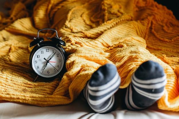 Menschen, die auf einem bett unter den decken und warmen socken mit wecker schlafen, der seitlich 7 uhr anzeigt