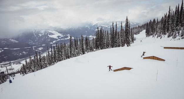 Menschen, die auf schneebedeckten alpen im skigebiet ski fahren