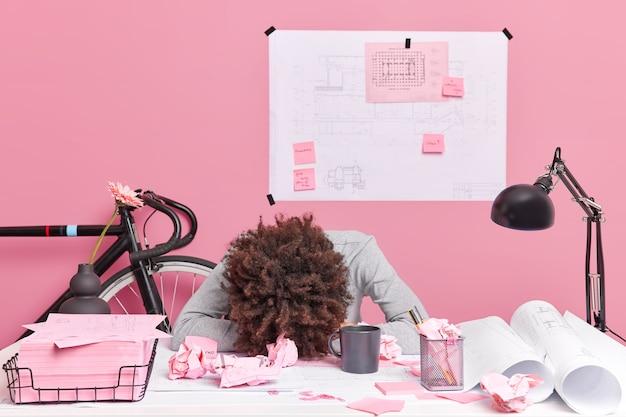Menschen, die das konzept der erschöpfungsfrist arbeiten. müde, lockige, überarbeitete frau lehnt sich am schreibtisch und arbeitet an einem zukünftigen projekt, umgeben von papierfetzen, skizzen, blaupausen, schlafmangel