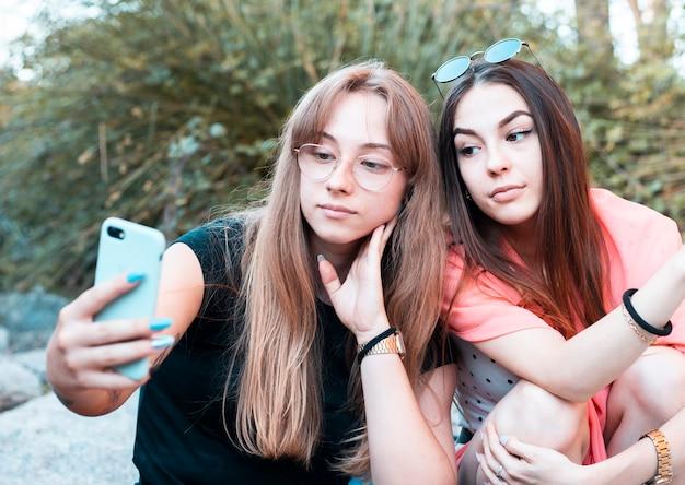 Menschen, die das smartphone im freien benutzen - freunde, die fotos machen