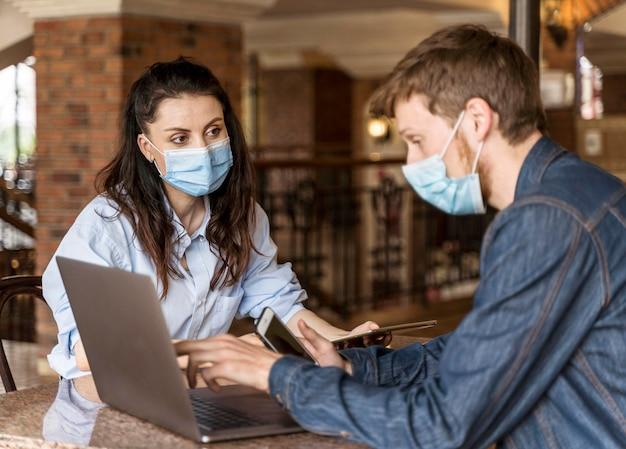 Menschen, die drinnen zusammenarbeiten, während sie medizinische masken tragen