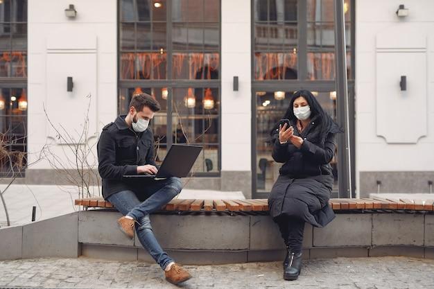 Menschen, die eine schutzmaske tragen, die in einer stadt mit elektronischen geräten sitzt