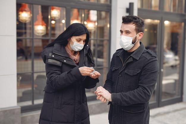 Menschen, die eine schutzmaske tragen, stehen auf der straße, während sie alkoholgel verwenden