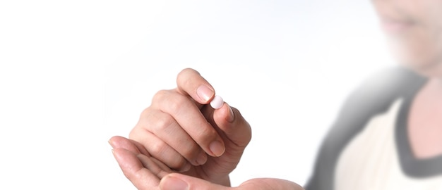 Menschen, die eine weiße medizinpille in der hand nehmen oder halten, die hilft und vor einem pandemievirus schützt