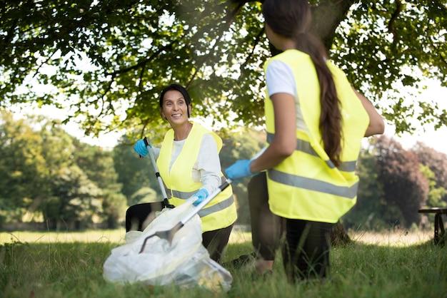 Menschen, die gemeinnützige arbeit leisten, indem sie müll in der natur sammeln