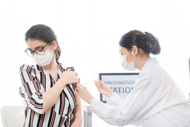 Menschen, die in einer klinik oder einem krankenhaus einen covid-impfstoff erhalten, tragen eine schutzmaske gegen covid19