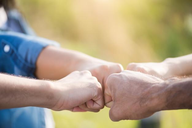 Menschen, die mit der faust stoßen, zeigen einheit und teamwork