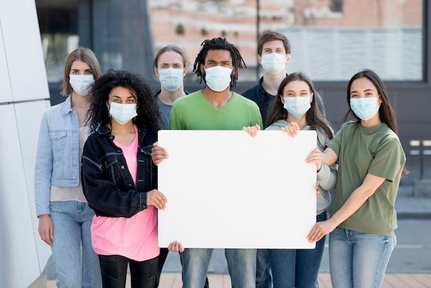 Menschen, die protestieren und medizinische masken tragen, kopieren den raum