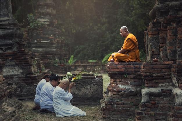 Menschen, die respekt vor einem mönch auf ayutthaya beten.