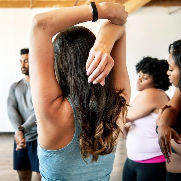Menschen, die sich in einem yogastudio dehnen