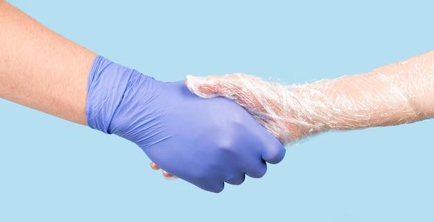 Menschen, die sich mit handschuhen die hand geben