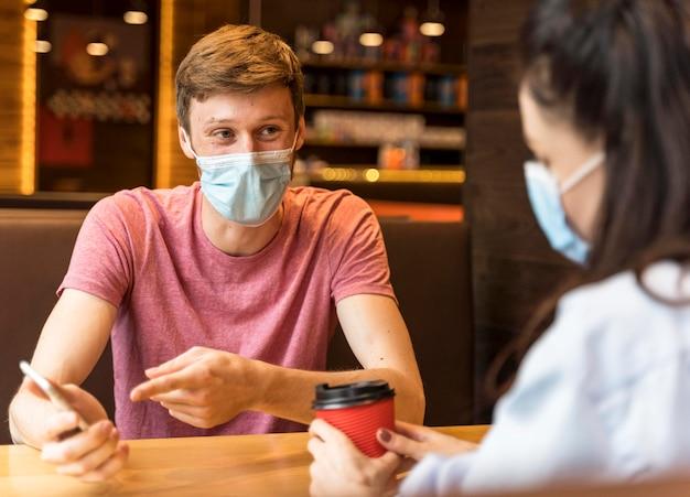 Menschen, die sich unterhalten, während sie drinnen medizinische masken tragen