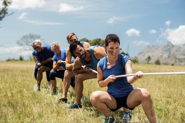 Menschen, die tauziehen während des hindernis-trainingskurses spielen
