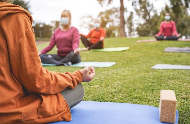 Menschen, die yoga-unterricht im freien auf gras sitzen, während sie sicherheitsmasken während des ausbruchs des coronavirus tragen