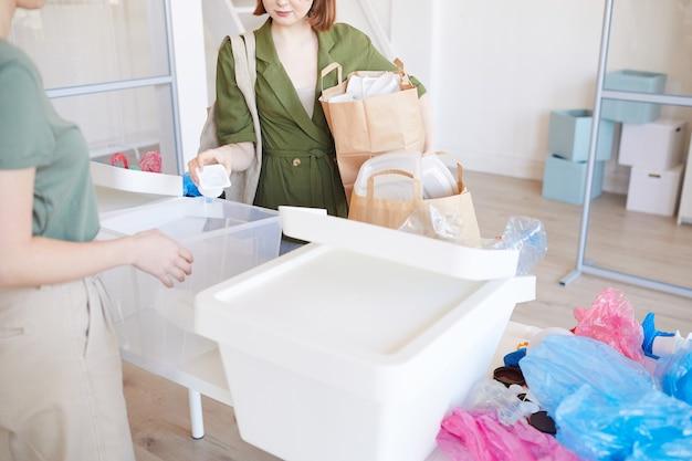 Menschen, die zu hause plastik sortieren, konzentrieren sich auf frauen, die papiertüten mit gegenständen bereithalten, die zum recycling bereit sind