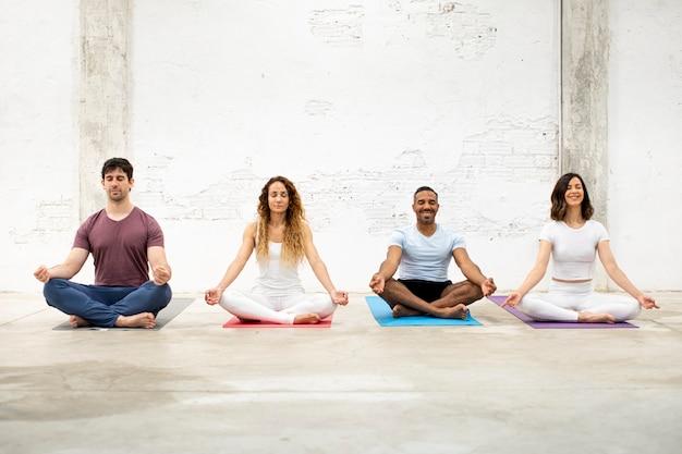 Menschen, die zusammen auf yogamatten meditieren