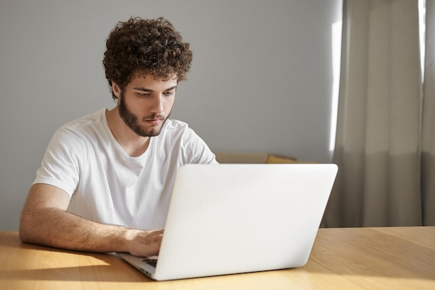 Menschen, elektronische geräte und technologiekonzept. ehrliche aufnahme eines ernsthaften gutaussehenden jungen männlichen freiberuflers, der kostenloses wlan auf dem laptop verwendet, während er von zu hause aus fernarbeitet und einen fokussierten blick hat