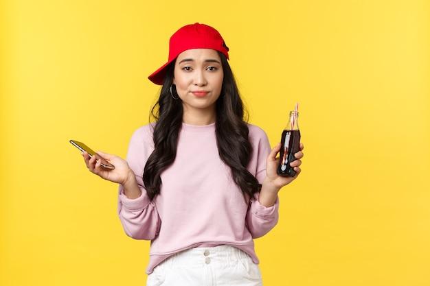 Menschen emotionen, getränke und sommerfreizeitkonzept. unentschlossenes ahnungsloses süßes asiatisches mädchen in roter kappe, das eine flasche mit soda und handy hält, unsicher zuckt, gelber hintergrund.
