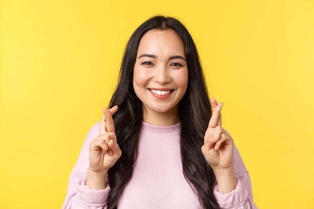 Menschen emotionen, lifestyle-freizeit- und schönheitskonzept. aufgeregte asiatische frau, die breit lächelt, kreuzfinger viel glück, wunsch verträumt, flehend oder glaubend, gelber hintergrund stehen.